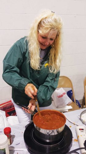 Submitted Photo A contestant during last year's Chili Cook-Off stirs a pot of cowboy chili. The second annual Chili Cook-Off is Oct. 7 at the North Dakota State Fair Center.