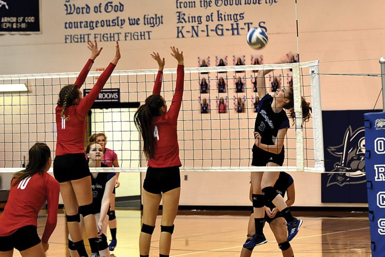 Garrick Hodge/MDN Our Redeemer's Karolynn Winger (3) goes for a kill while Des Lacs-Burlington's Kyley Lauf (11) and Alyea Casavant (4) try for a block during a high school girls volleyball game Tuesday in Minot. ORCS won the match 3-0.