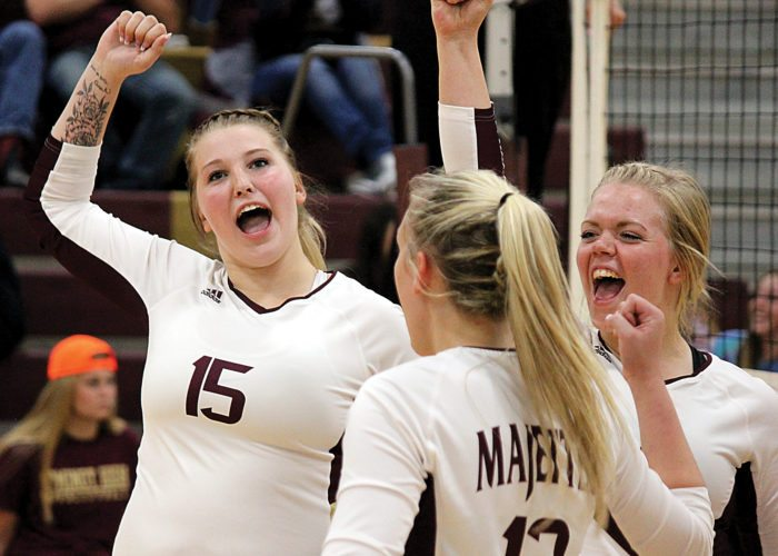 Alex Eisen/MDN Minot High senior Abbie Jarmin (15) and Kali Askvig (right) celebrate after a point scored Tuesday in a West Region match against Williston at Minot High School.