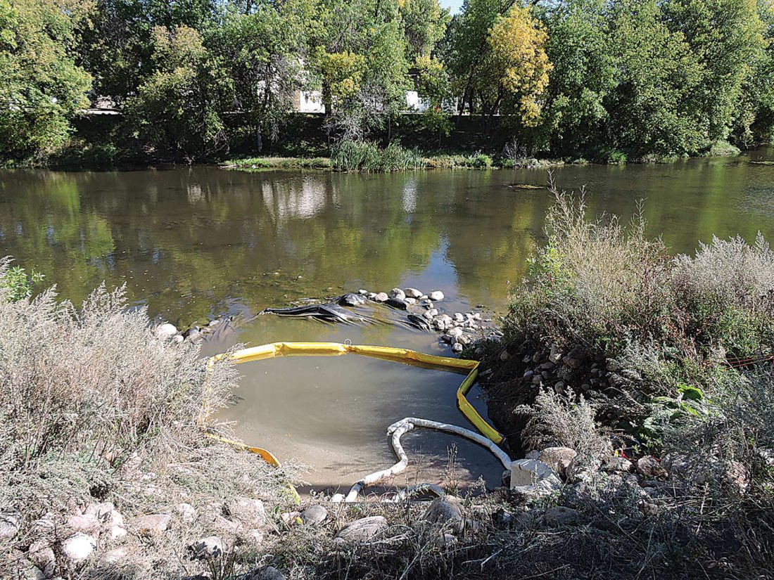 A yellow collection boom designed to contain a spill of diesel fuel lies on the water of a dead loop of the Souris River. The fuel leak was first noticed about noon Tuesday in the area where the county's new jail in being constructed.  Kim Fundingsland/MDN