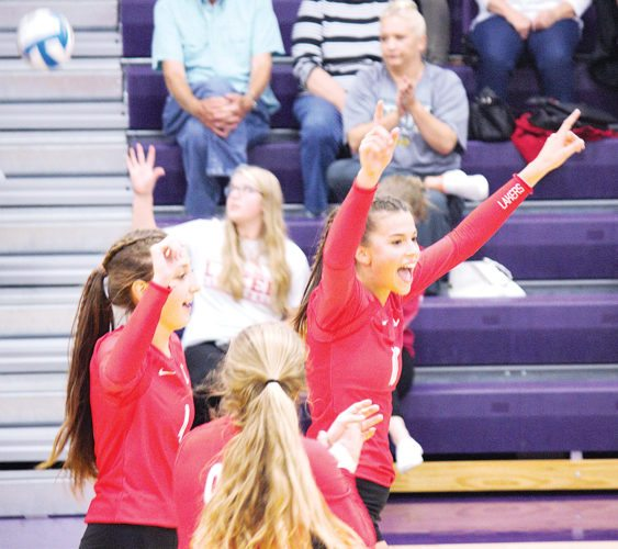 Alex Eisen/MDN Des Lacs-Burlington senior setter and outside hitter Caitlyn Vogel (10) throws both arms up in the arm after scoring a point Thursday in a match against Bishop Ryan in Minot.