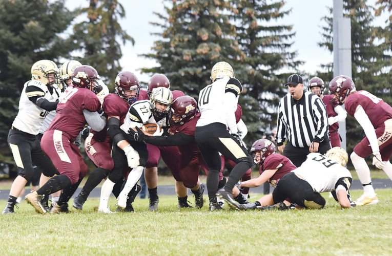 Garrick Hodge/MDN A swarm of Minot High defenders make a tackle during a high school football game Friday at Duane Carlson Stadium in Minot.