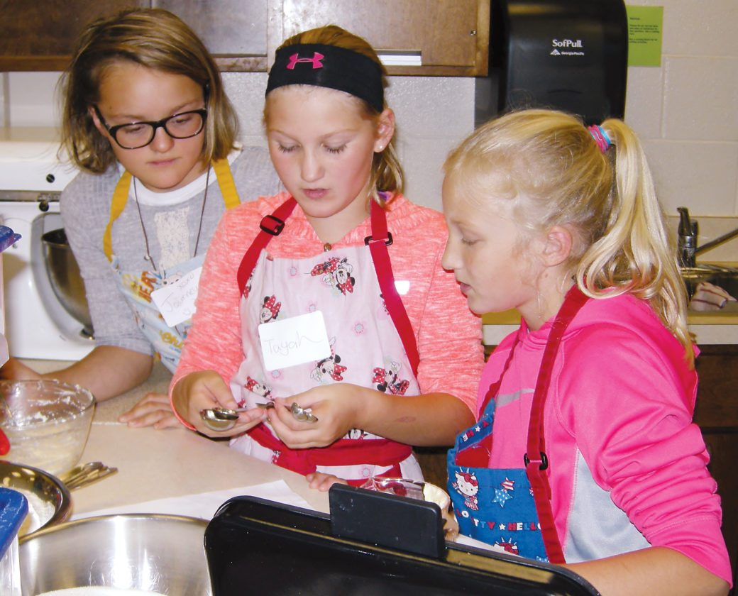 Andera Johnson/MDN Journey Larson, Tayah Westerness and Kassidy King look at measuring cups while making krumkake during the Scandinavian Youth Camp Saturday.