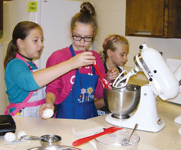 Andrea Johnson/MDN Katie Wiekamp, Cadynn Crockett and Sophie Bell mix batter for krumkake, or Norwegian bent cake, during the Scandinavian Youth Camp on Saturday afternoon.