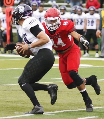 Garrick Hodge/MDN Minot State's Elijah Mosley (44) sacks Winona State quarterback Owen Burke.