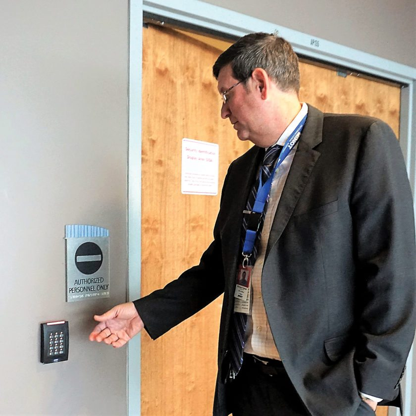 Jill Schramm/MDN Minot Airport Director Rick Feltner, wearing his identification badge, reaches toward an electronic badge reader, which is part of securing restricted areas from unauthorized access