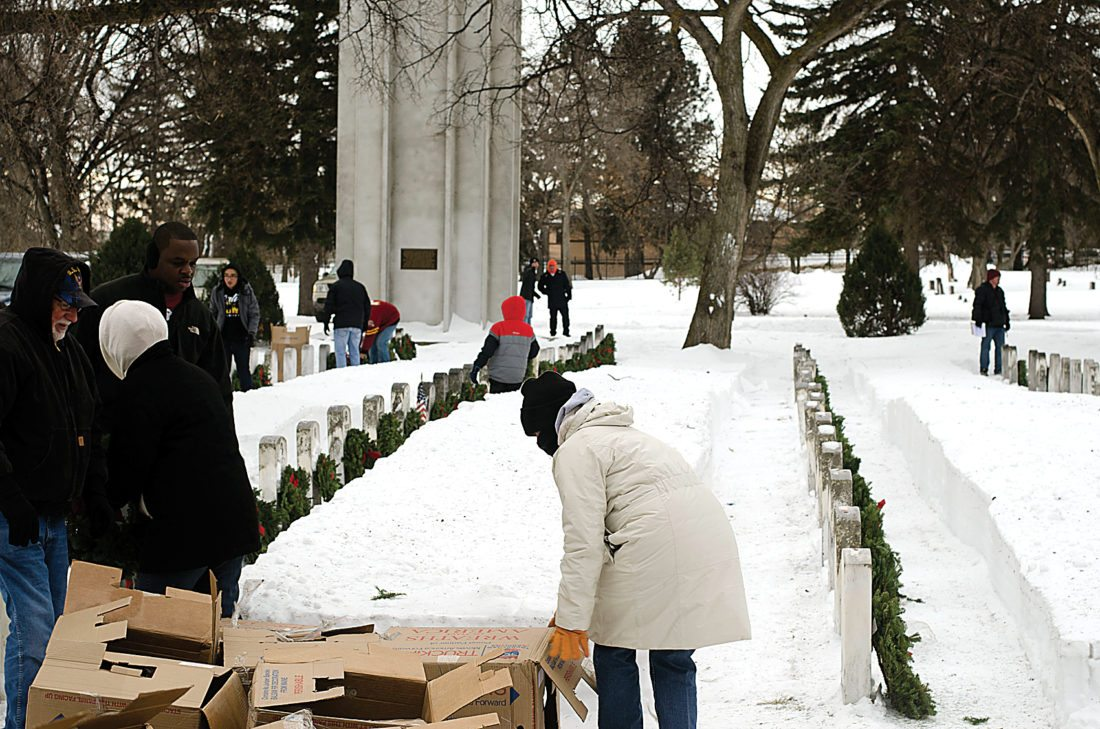Submitted Photo Volunteers place wreaths in Section 12 (Old Veterans Section) in Rosehill Memorial Park during the 2016 Wreaths Across America program. This will be the fourth annual year for the program in Minot.