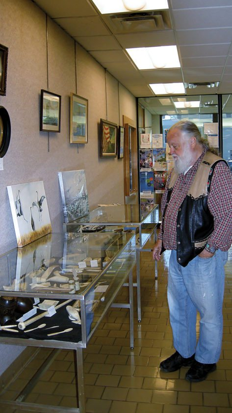 Andrea Johnson/MDN Steve Holmes of Garrison looks at items from a collection of whaling history artifacts that are on display at the Minot Public Library.