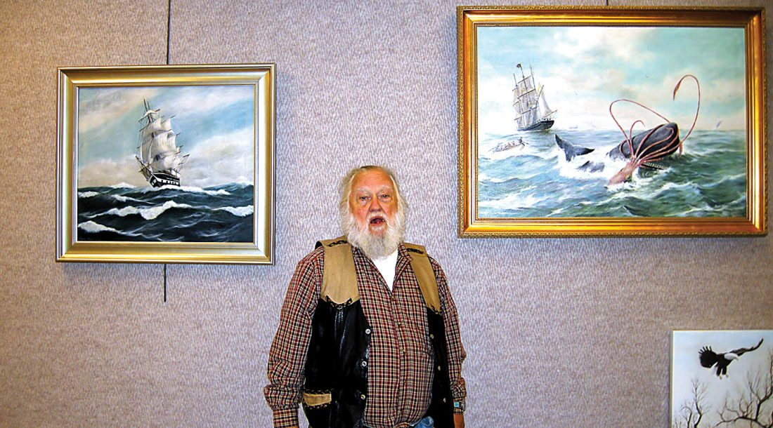 Andrea Johnson/MDN Steve Holmes poses beside some of his paintings on display at the Minot Public Library.