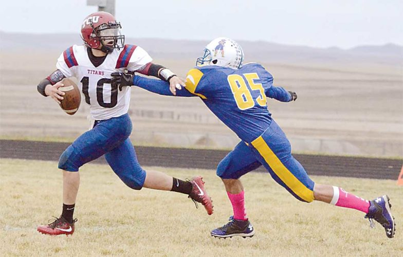 Parker Cotton/The Dickinson Press Beach junior linebacker Jared Wojahn (85) chases after TGU quarterback Garrett Bailey (10) on Saturday in the opening game of the 9-man football playoffs.