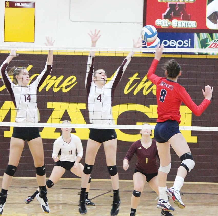 Alex Eisen/MDN Minot's Caitlyn Messner (14) and Elise Klein (4) go up to block Century's Megan Anderson (9) in a West Region match played Tuesday at Minot High School. The Patriots won 3-0.