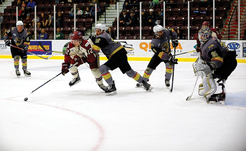 Submitted Photo Minot's Austin Dollimer (12) tries to control the puck in Bismarck's zone. Photos courtesy of Steve Silseth.