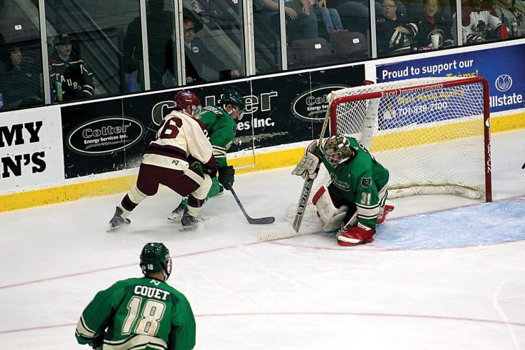 Garrick Hodge/MDN Minot's Jed Pietila (26) fights for the puck in Minnesota's zone Friday at Maysa Arena. The Minotauros won 5-3 Friday.
