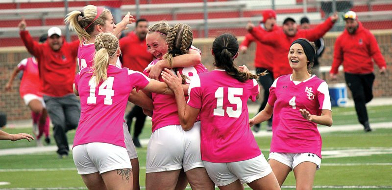 Alex Eisen/MDN Minot State freshman forward Morgan Myers gets swarmed by her teammates after scoring the game-winning goal in double overtime Sunday against No. 13-ranked Minnesota State Mankato at Herb Parker Stadium.