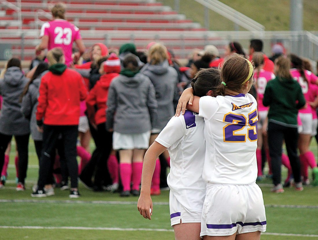 Alex Eisen/MDN Minnesota State Mankato's Lexi Pszanka (25) hugs her teammate while Minot State golden goal scorer Morgan Myers (23) is lifted onto her teammates shoulders Sunday at Herb Parker Stadium.
