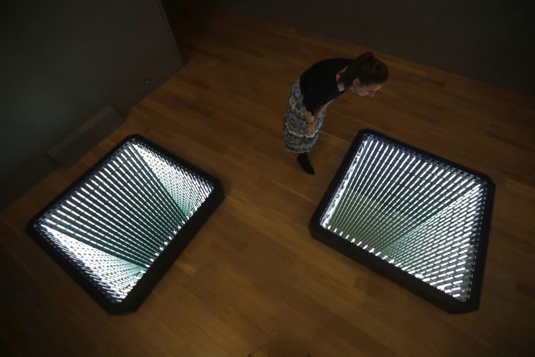 """A staff member poses for photographs looking at Chilean-born artist Ivan Navarro's two light box and mirror installation """"The Twin Towers"""" during the media preview for the """"Age of Terror: Art since 9/11"""" exhibition at the Imperial War Museum in London, Wednesday, Oct. 25, 2017.  The exhibition, which runs from Oct. 26 until May 28, 2018, considers artists' responses to war and conflict since the attacks of Sept. 11, 2001. (AP Photo/Matt Dunham)"""