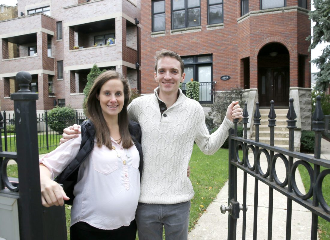 In this Sunday, Oct. 15, 2017, photo, Emily and Brian Townsend pose outside their home where they own the top floor unit in a three-flat building in Chicago. (AP Photo/Charles Rex Arbogast)