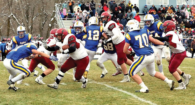 Submitted Photo LAEM senior running back Connor Tetrault (44) stiff arms a Velva defender Saturday in the state semifinals in Velva. Photo courtesy of Al Christianson