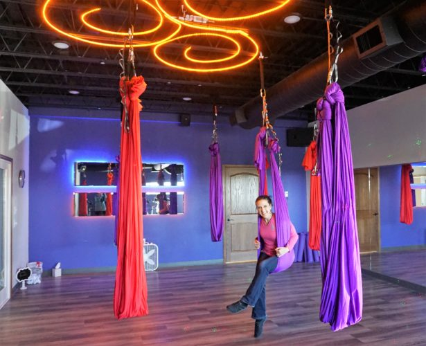 Jill Schramm/MDN  Rachelle Sian with Spectrum Fitness sits Oct. 20 in one of the aerial silks that are used in aerial yoga at the center.