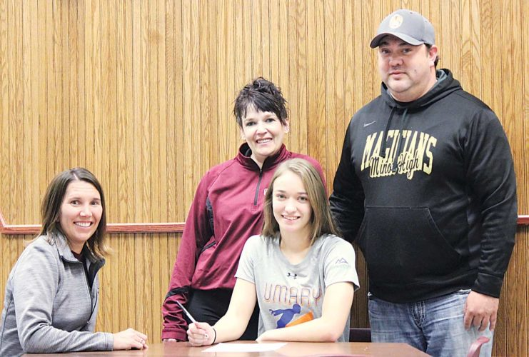 Alex Eisen/MDN Minot High senior Alli McCoy signs a National Letter of Intent to the University of Mary with coach Melissa Solper (left) and her parents Charlene and Tom McCoy (standing) in attendance.