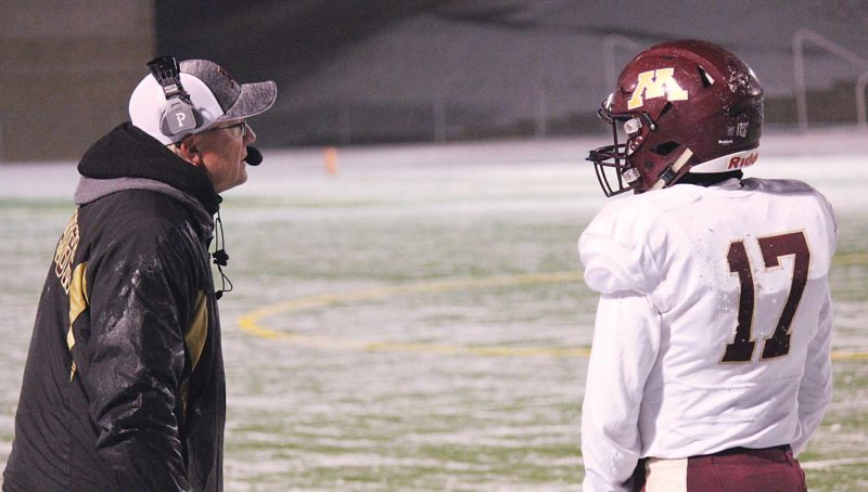 Alex Eisen/MDN Minot High football coach Barry Holmen (left) gives Magicians senior quarterback Creighton Rudolph (17) the play to run during the Class 11AAA state semifinals last Friday in Bismarck.