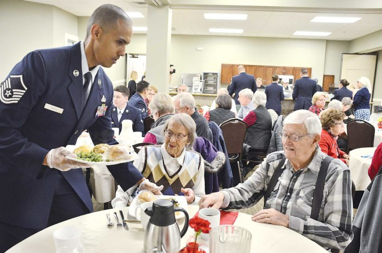 Eloise Ogden/MDN Master Sgt. Javier Parris, left, of the 5th Communications Squadron at Minot Air Force Base, serves the noon meal to World War II veteran Norman Abernathey, right, and his wife, Gladys, center, following the Veterans Day program at the Parker Senior Center in Minot on Thursday. About 25 Minot Air Force Base active-duty members served the meals that day to the veterans and others.