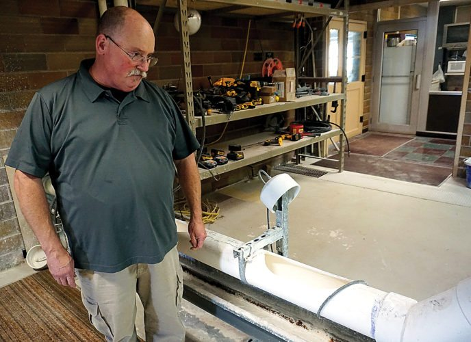Jill Schramm/MDN Water Treatment Plant foreman Mark Paddock watches a lime and water mixture flow through a trough toward a treatment basin in the plant Tuesday. The idea of local preference took hold during a city council debate over a lime supply contract.