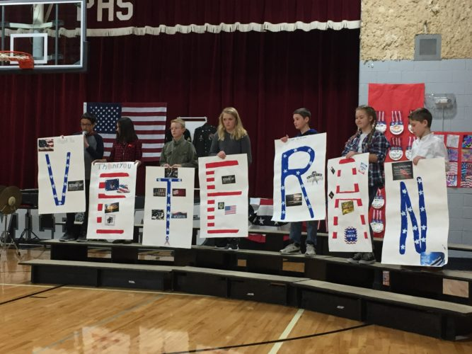"""Submitted Photos Sixth-grade students at North Shore Plaza School hold up letters spelling """"veteran"""" during the school's annual Veterans Day Tribute held at the school Thursday. From the left are Isaiah Robles, Mackenzie Woodard, Colton Davison, Hannah Braaflat, Tadyn Hathaway, Peyton Alford and Kaian Enockson. Local veterans from the Makoti and Plaza Legion clubs were honored. At the annual event each of the elementary classrooms has a part in the program and the high school band also plays. After the program everyone has cake with the veterans and visit."""