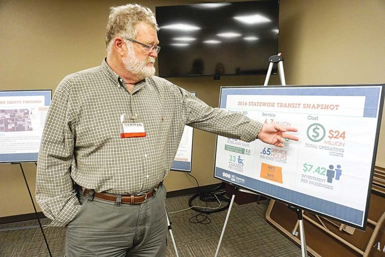 Jill Schramm/MDN Steven Mullen with the North Dakota Department of Transportation points out statistics on transit ridership in 2016 at a public open house in Minot Wednesday.