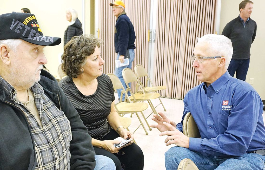 Jill Schramm/MDN Kevin Bluhm with the Corps of Engineers visits with Warren and Liz Hoppmann at a public meeting on flood protection Thursday.