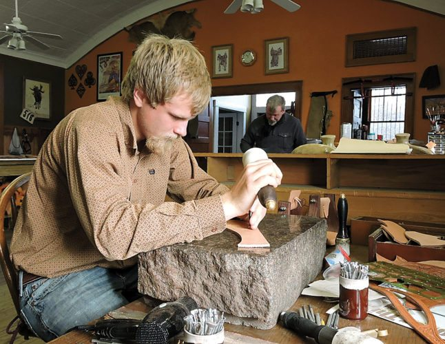 Kim Fundingsland/MDN Jack Kramer carefully tools a design into a piece of leather while his father applies varnish to the top of the cantle of a custom saddle.