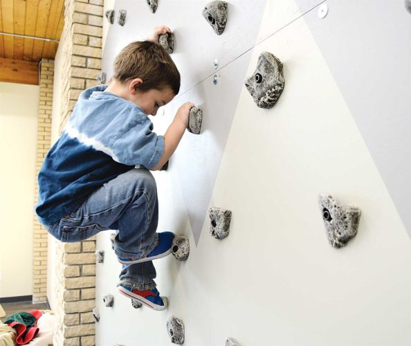 Submitted photo A young boy, Tytus, maneuvers the climbing wall in the new sensory gym at Caleb's Clubhouse.
