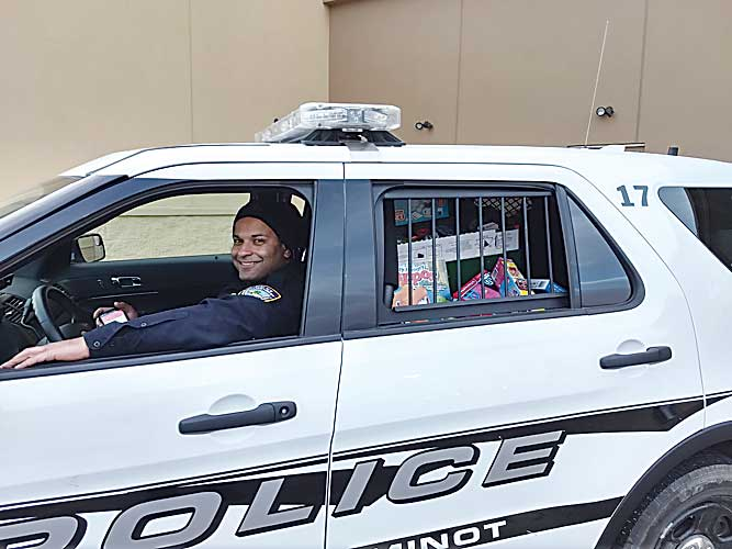 Minot Officer James Jabara sits behind the wheel of a police vehicle stuffed with toys.  Submitted Photo