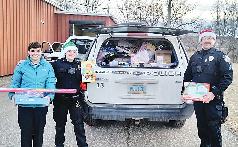 Minot Police Sgt. Paul Burns, right, and officer Heather Summers, along with Police Explorers Post member Emily McCabe, left, show some of the toys collected Sunday.