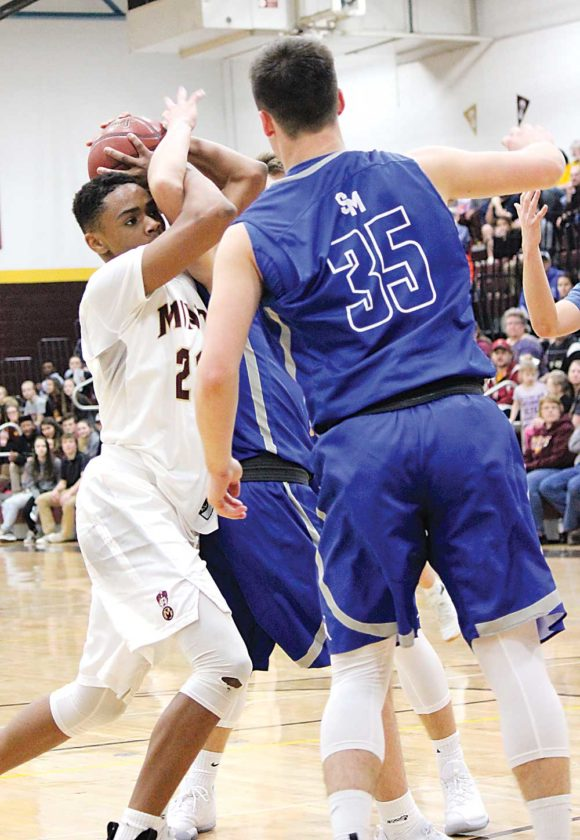 Alex Eisen/MDN Minot High sophomore Devin Mikell (left) gets tangled up with a couple of Bismarck St. Mary's players while driving to the basket Tuesday in Minot's home opener.