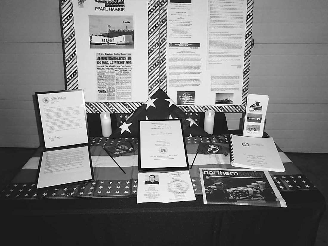 """Submitted Photo Memorabilia is on display today in the lobby of the Grand Hotel in Minot in commemoration of Pearl Harbor Day today. On Dec. 7, 1941, Japanese aircraft attacked the U.S. Navy's base at Pearl Harbor, Hawaii. A single rose will be added to the display shown here. """"The purpose of this display is to share with our community the history of the Pearl Harbor attack and to remember those who have sacrificed their lives for our freedom today,"""" said Richard Reuer, public relations officer for the Minot American Legion Post."""