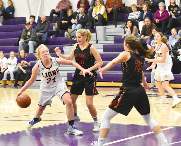 Garrick Hodge/MDN Bishop Ryan's Emma Passa (34) drives to the lane while Rugby's Tristin Lunde (12) defends during a high school girls basketball game Friday in Minot. The Lions won 49-46.