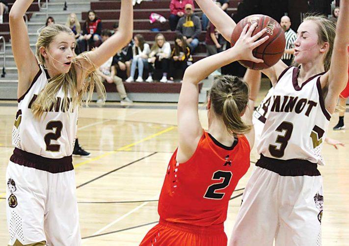 Alex Eisen/MDN Minot High sophomore Allie Nelson (2, left) and sophomore Paige Rosencrans (3) trap Dickinson's McKenna Weiler (2) in a WDA girls basketball game played Saturday at Minot High School.