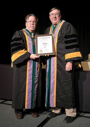 Submitted Photo Dr. Mark Hildahl, right, is inducted as a Fellow of the International College of dentists.