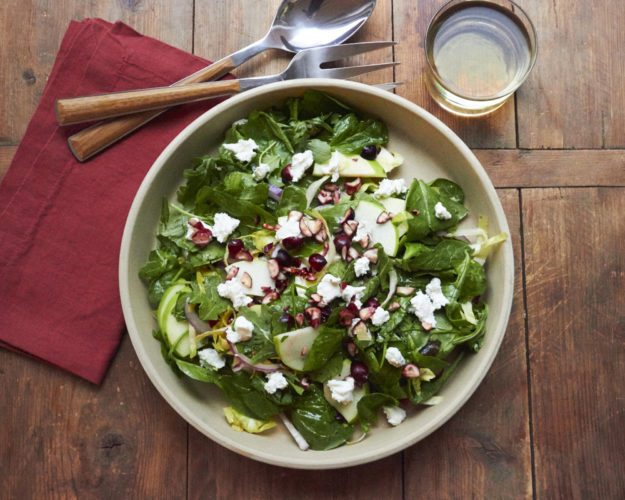 This October 2017 photo shows a winter green salad with cranberries and goat cheese in New York. This salad comes together in 20 minutes, and is a bowl of vibrant color and texture that seems anything but a postscript to the menu. (Mia via AP)