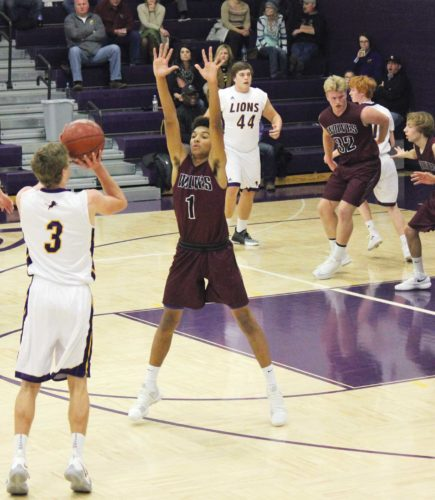 Alex Eisen/MDN Bishop Ryan junior guard Ben Bohl (3) takes a shot from long range over Watford City's Elijah Brown (1) Tuesday at Bishop Ryan Catholic School in Minot.