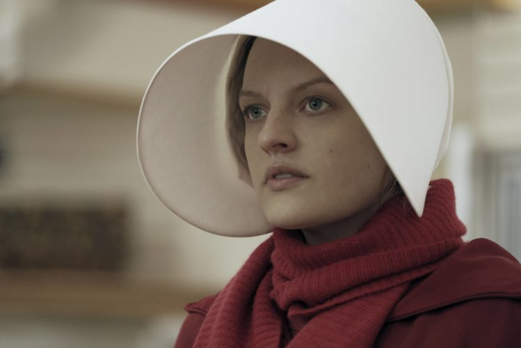 "This image released by Hulu shows Elisabeth Moss as Offred in a scene from, ""The Handmaid's Tale."" Moss portrays one of the few remaining fertile women in the cruel futuristic dystopia of Gilead, a totalitarian society where human rights are trampled and this special caste of women is forced into sexual servitude in a desperate attempt to repopulate a ravaged world. (George Kraychyk/Hulu via AP)"