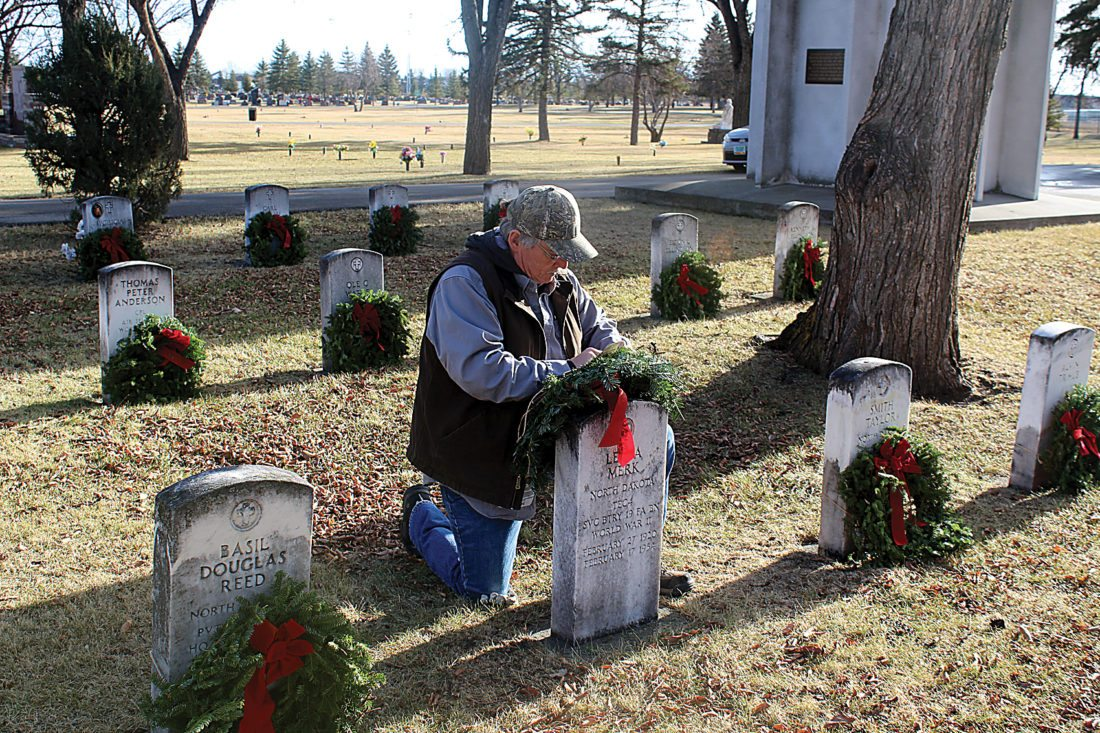 Ashton Gerard/MDN Minot resident Randy Davis works to secure a wreath Saturday at the Rosehill Memorial Park. He attended the ceremony with his wife, Brenda Davis.