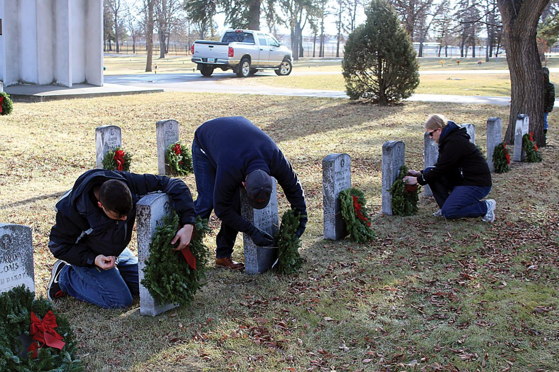 Ashton Gerard/MDN  Senior Airman Dakota Asselyn and Staff Sgt. William Tucker work alongside Lisa Peckham to secure wreaths during the Wreath Laying Ceremony Saturday at Rosehill Memorial Park. Dec. 16 marked the National Wreaths Across America Day for 2017.