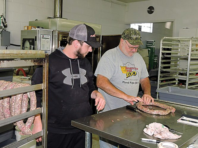 Kim Fundingsland/MDN Venison sausage remains popular with North Dakota deer hunters. Here Scott Wald, left, and his father, Brian, prepare rope sausage for the smoker at Valley Custom Meats located on Highway 2/52 immediately west of Minot.