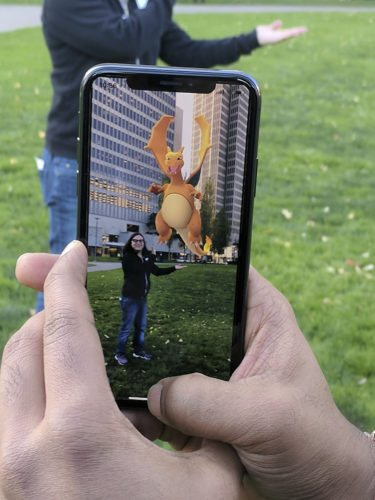 In this Monday, Dec. 18, 2017, photo, Pokemon Go is played at a park in San Francisco. Pokemon Go is unleashing its digital critters in Apple's playground for augmented reality, turning iPhones made during the past two years into the best place to play the mobile game, according to the CEO of the company that makes Pokemon Go. (AP Photo/Michael Liedtke)