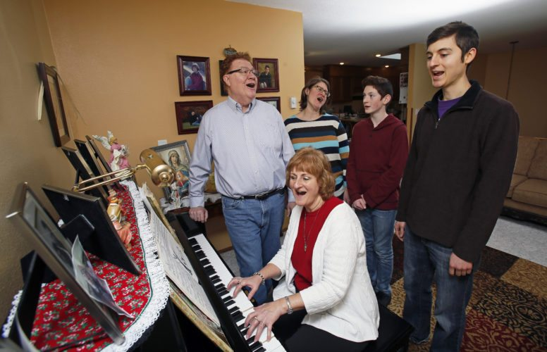 John and Jan Klocke sing Christmas carols with their daughter, Laura Devick and grandson Max, and son John R. Klocke, in the family home in south Fargo.  David Samson / The Forum