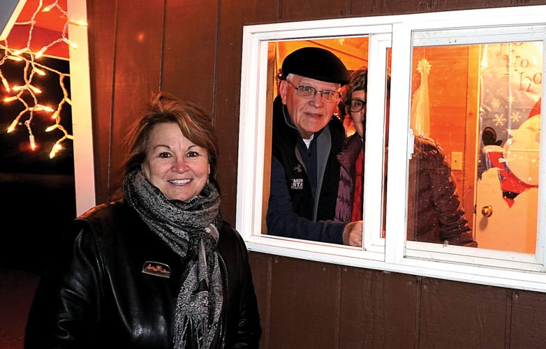 Jill Schramm/MDN Sue Stewart stands next to the Sertoma hut, manned on Dec. 13 by 49-year Sertoma member Dale Mattern and his wife, Kay, at the entrance to the Oak Park lighted display