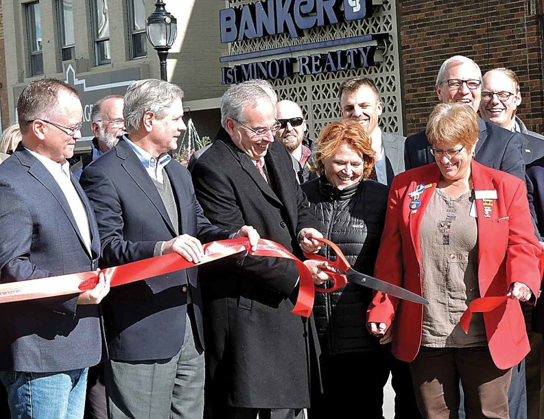 Kim Fundingsland/MDN Minot Mayor Chuck Barney, center, cuts the ribbon celebrating the completion of the downtown Minot improvements project.