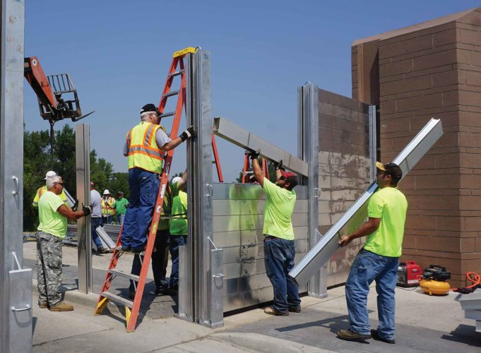 City Public Works employees practice erecting the floodwall closure across 16th Street near the water treatment plant in July.  Jill Schramm/MDN